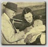 Proud parents John Farrow and Maureen O'Sullivan playing with baby Michael