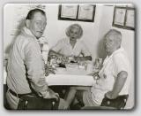 John Wayne, John Farrow, and Lana Turner having lunch.
